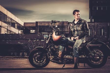 Biker en zijn bobber stijl motorfiets op een stad straat