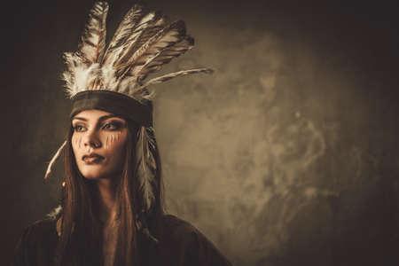 伝統的なインディアンの頭飾りと顔のペイントを持つ女性