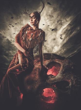 Woman shaman in ritual garment siting on skull Standard-Bild