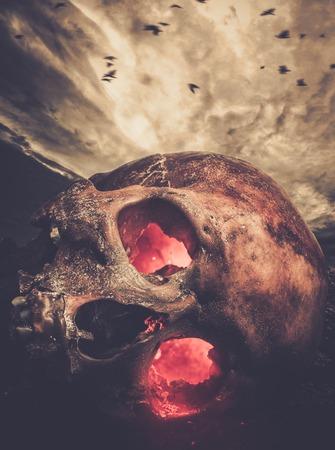Menschlicher Schädel mit glühenden Augen gegen stürmischen Himmel Standard-Bild - 38936543