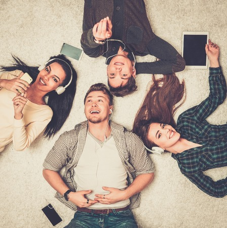 Happy multiracial friends relaxing on a carpet with gadgets Foto de archivo