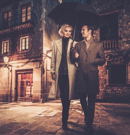 Elegant paar met paraplu lopen buiten in de regen Stockfoto