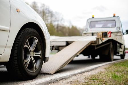 Laden kapotte auto op een sleepwagen op een langs de weg