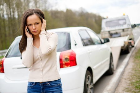 女性ながら彼女の車を拾ってレッカー車 写真素材