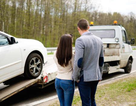 Couple near tow-truck picking up broken car 스톡 콘텐츠