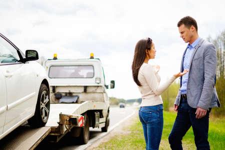 Couple near tow-truck picking up broken car Reklamní fotografie