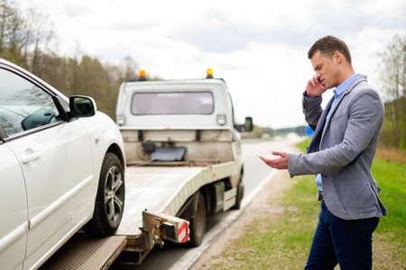 견인 트럭이 그의 깨진 된 차를 따기 동안 남자 호출