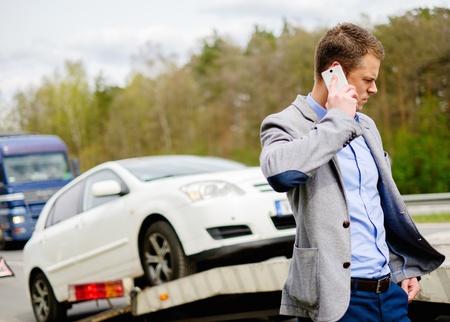 Man bellen terwijl sleepwagen oppakken van zijn gebroken auto Stockfoto