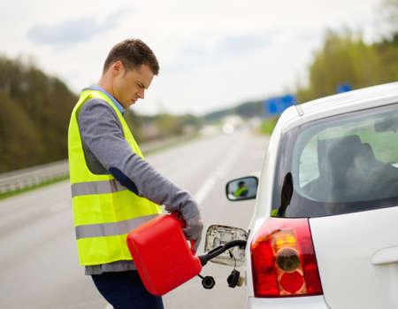 Man refuelling her car on a highway roadside