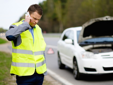 Man calling car towing service on a highway roadside