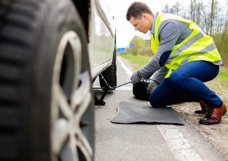 Man changing wheel on a roadside