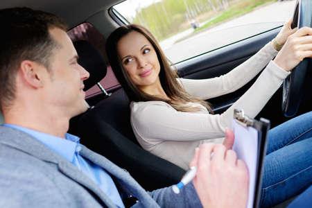 講師と女性学生を試験車の運転 写真素材