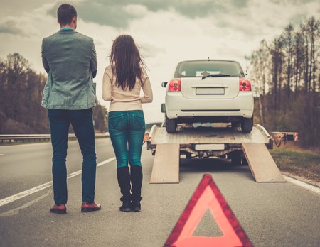 Couple near tow-truck picking up broken car Stockfoto