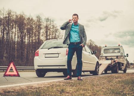 Man appel tout en dépanneuse ramassant sa voiture cassée Banque d'images - 39952324