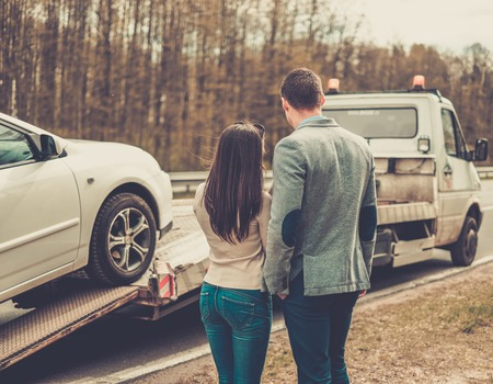 Couple near tow-truck picking up broken car Stock Photo