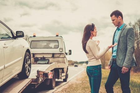 レッカー車は壊れた車を拾って近くのカップル 写真素材