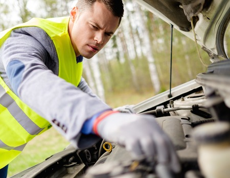 Man fixing broken car on a roadside