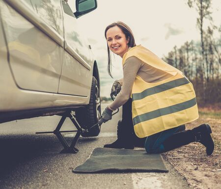 Woman changing wheel on a roadside Stock Photo