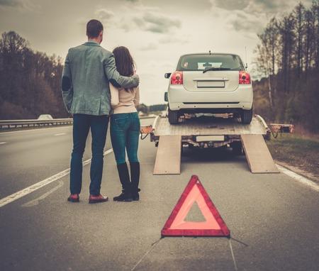 Couple near tow-truck picking up broken car Standard-Bild