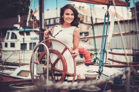 Stylish wealthy woman on a luxury wooden regatta Stok Fotoğraf