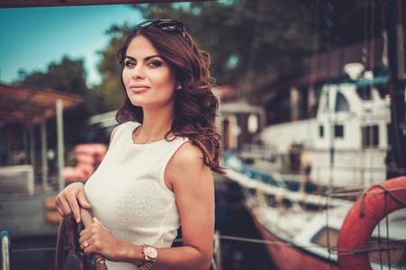 高級木製レガッタのスタイリッシュな裕福な女性 写真素材