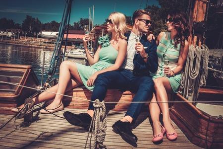Amigos ricos con estilo que se divierte en un yate de lujo Foto de archivo - 41847409