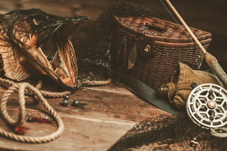 Fishing tools and pikes head on a wooden table
