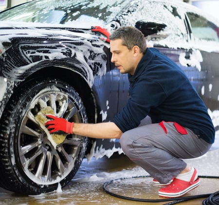 Mensenarbeider wassen van auto's lichtmetalen velgen op een wasstraat