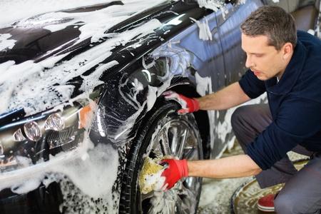 洗車で車のアルミ ホイールを洗う男性労働者