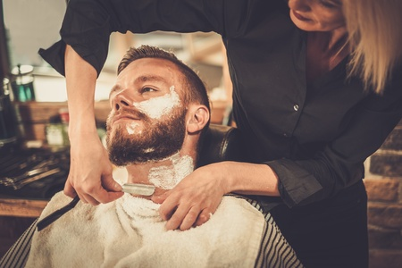 Client during beard shaving in barber shop Banco de Imagens