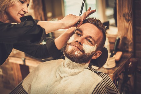 Client during beard shaving in barber shop Stock Photo
