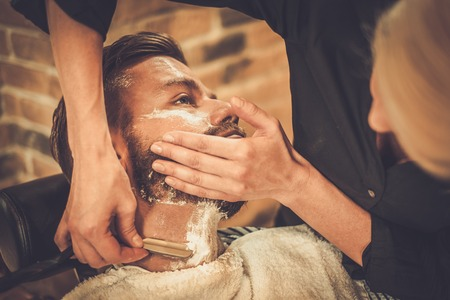 Client during beard shaving in barber shop Stockfoto