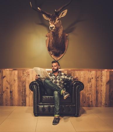革張りの椅子で新聞を読む中年のヒップスターのガラスがウイスキーの