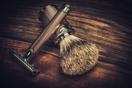 Safety razor and shaving brush on a wooden background