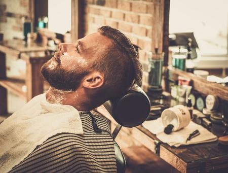 理髪店で髭剃り中のクライアント 写真素材