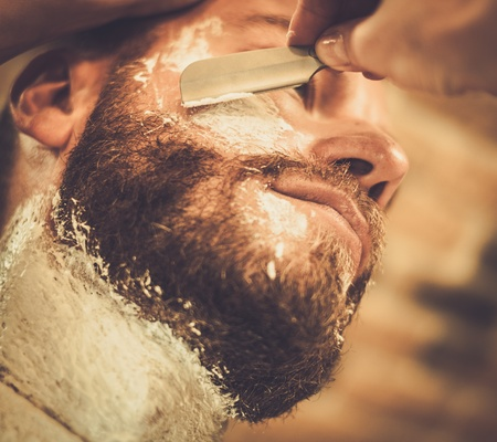 Client during beard shaving in barber shop Stok Fotoğraf
