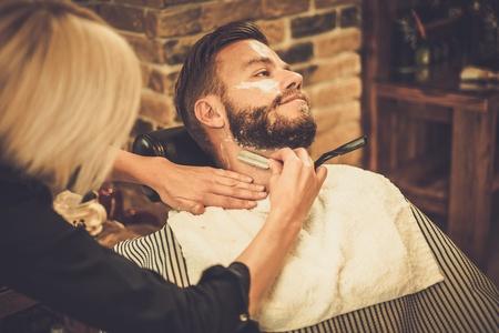 Client during beard shaving in barber shop 版權商用圖片