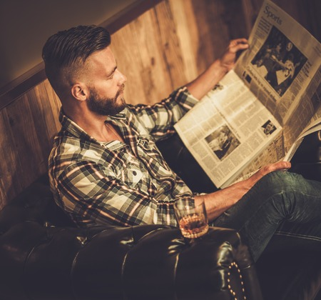 Middle-aged hipster reading newspaper on leather sofa in barber shop Imagens