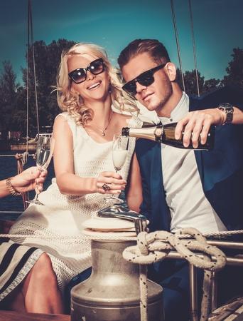 Stylish wealthy couple on a luxury yacht