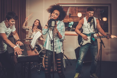 Multiracial music band performing in a recording studio Stock fotó - 43227823