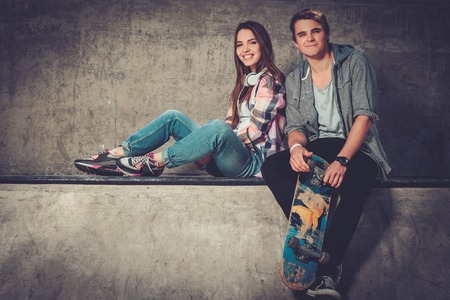 Young couple with skateboard outdoors
