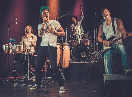 Multiracial music band performing on a stage Standard-Bild
