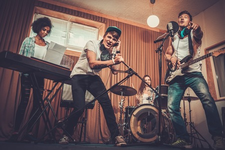 Multiracial music band performing in a recording studio Stok Fotoğraf - 43589305