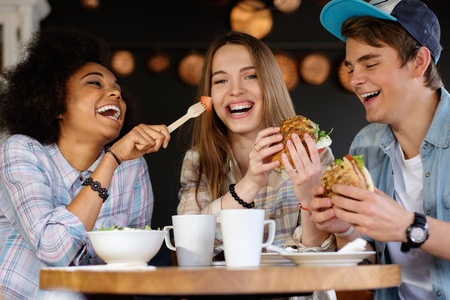 Vrolijke multiraciale vrienden eten in een cafe Stockfoto