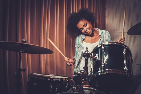 Black woman drummer in a recording studio