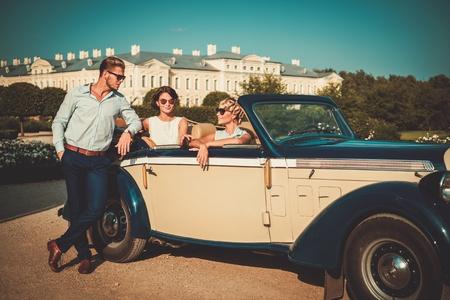Amigos ricos en un clásico palacio real cerca convertible