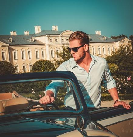 Zelfverzekerd rijke jonge man achter klassieke cabriolet stuurwiel Stockfoto