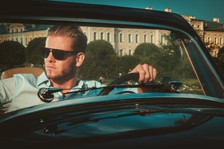 Joven rico Confiado detrás clásico volante convertible