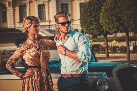 Riche couple près convertible classique contre le palais royal Banque d'images - 44242498