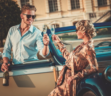 Wealthy couple with champagne near classic convertible